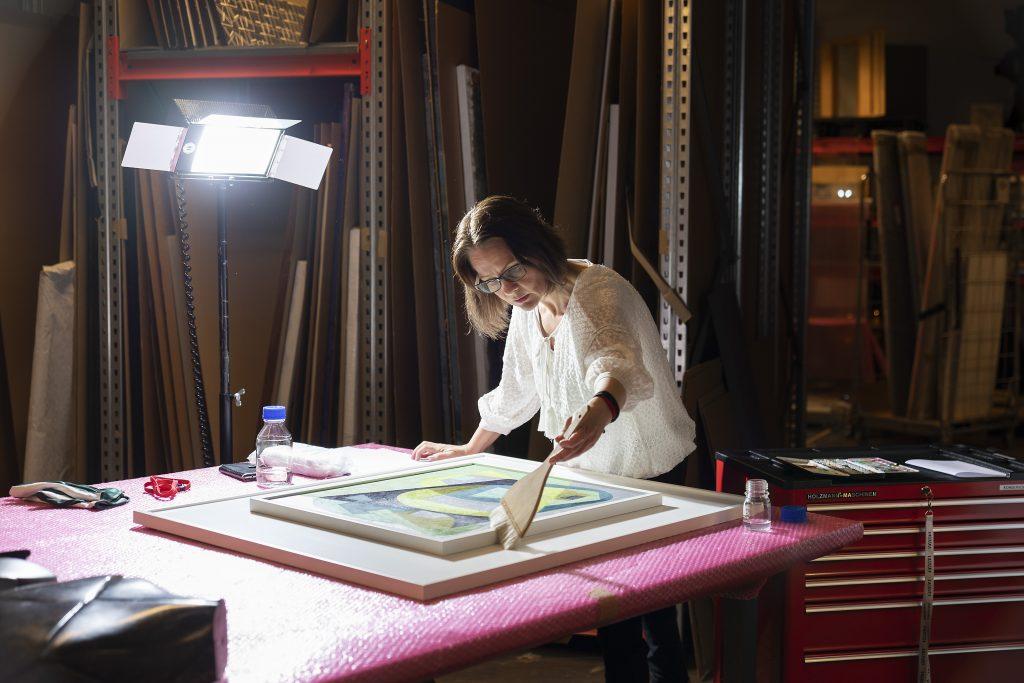 Konservaattori konservoimassa pitkäaikaislainaksi sijoitettavaa taideteosta.