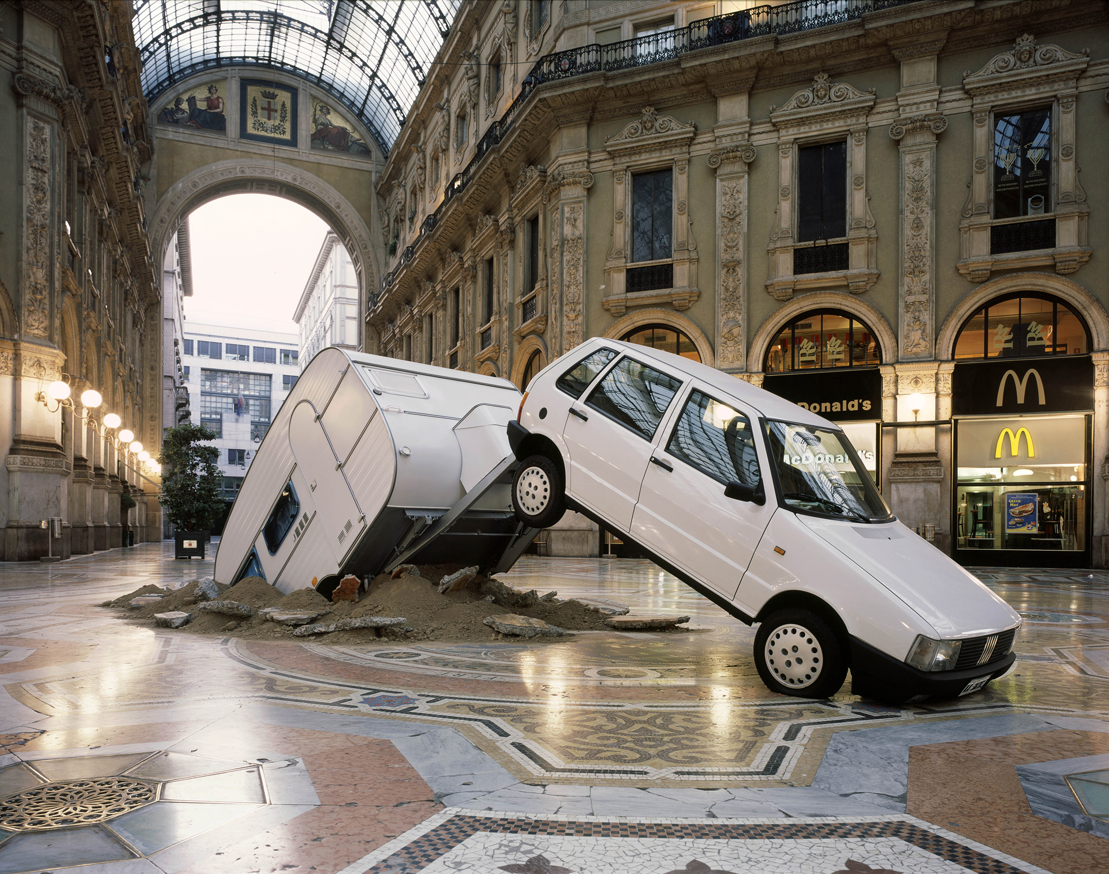 Elmgreen & Dragset artwork where a Fiat Punto caravan has crashed an italian public square in Milan.